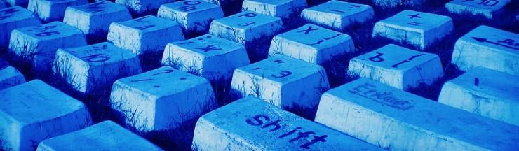 blue-computer-keyboard-stones-on-grass-background-header